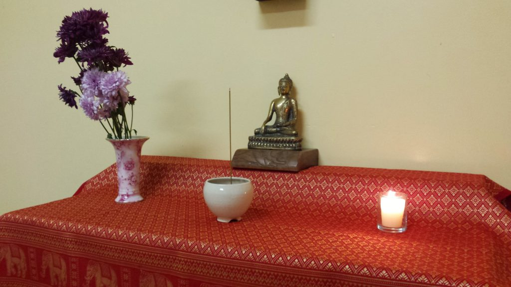 A Buddhist altar with Buddha statue, flowers, incense burner and candle, set up in St. James Episcopal church in San Francisco, CA.